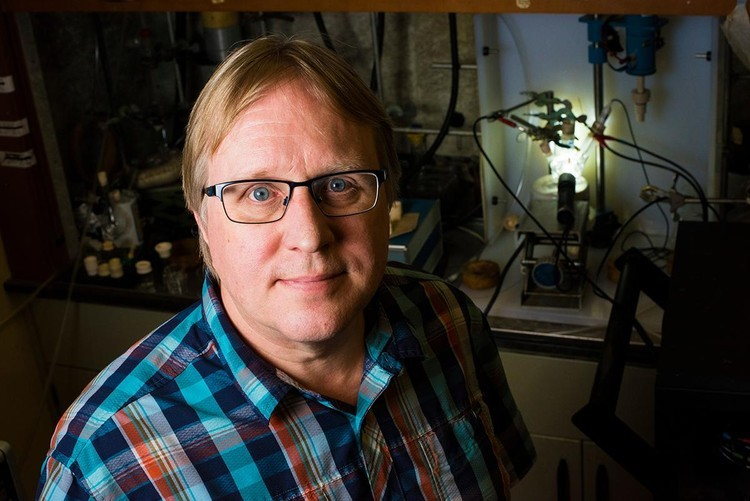 Steven Bergens, professor and chemist, is developing a catalyst that will turn carbon dioxide into useful molecules, like fuel, using light and water. Photo credit: John Ulan